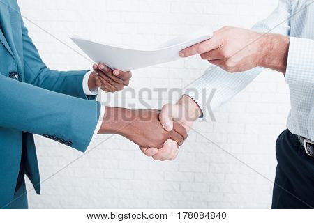 Handshake in office after making deal. Two owners of business signed contract about interracial cooperation.