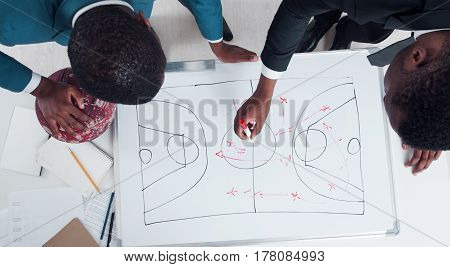Two american basketball coaches plan and discuss new game strategy. Trainers of student team making scheme of basketball game on the white board.