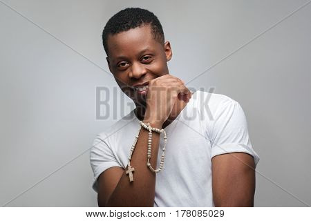 Portrait of smiling young african american man on grey background with freespace. Happy emotions, joy, gladness, good luck.