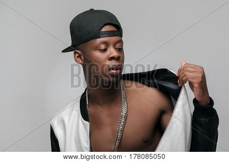 Young afroamerican rapper in hip-hop outfit on grey background with free space. Problem of substance abuse, crime, social issues, drugs. Ghetto, challenge to society, cheeky, cool, rebellious.