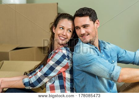 Young couple sitting back to back and looking at each other in their new house