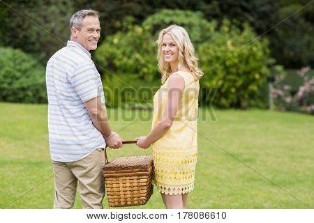 Happy couple holding picnic basket outside