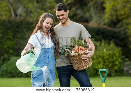 Woman watering a plants while man holding basket of vegetables in garden