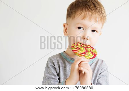 A boy eating lollipop. Happy kid with a big candy isolated on white background. Small child eating lollipop.