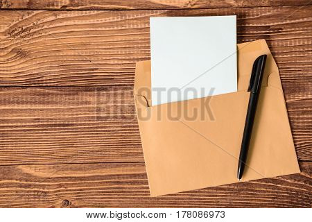 empty sheet of paper with pen and envelope on wooden background