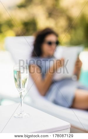 Close-up of champagne flute on side table and woman relaxing on background