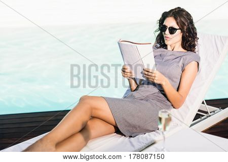 Young woman reading magazine and relaxing on a sun lounger near poolside