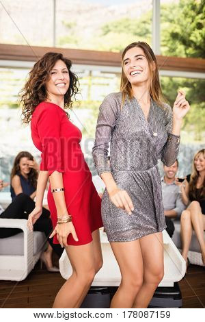 Two women dancing and group of friends watching their dance at party