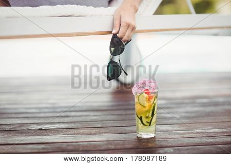 Close-up of womans hand holding sunglasses behind cocktail