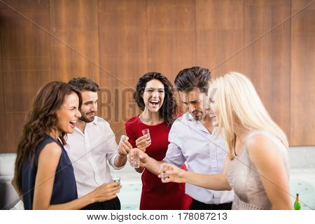 Young and handsome group of friends drinking shots at the party