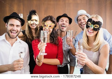 Friends with masks on holding champagne glasses laughing at camera