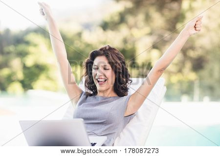 Excited young woman using laptop near poolside sun lounger