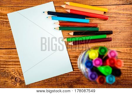 Wooden desk table with notebook, color pens. Top view with copy space