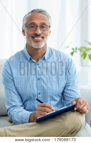 Portrait of happy doctor writing on a clipboard at home