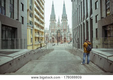 young tourist shoot old ghotic church in the middle of modern city