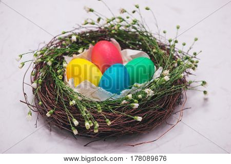 Easter eggs in beautiful nest on marble background.