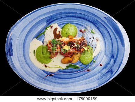 Chicken fillet on blue porcelain plate isolated over black background