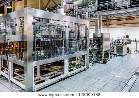 Automatic filling machine. Pouring beer in a brewery. Toned image