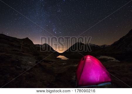 Camping Under Starry Sky And Milky Way Arc At High Altitude On The Italian French Alps. Glowing Tent