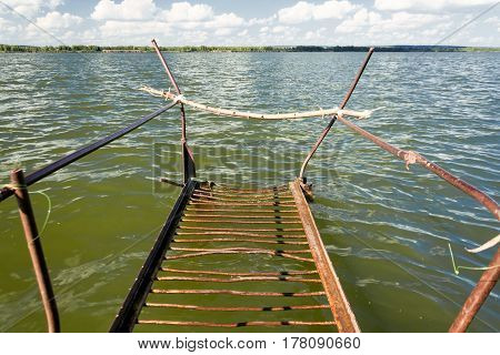 Old rusty metal footbridge on the lake. Sunny day, blue sky and green water.