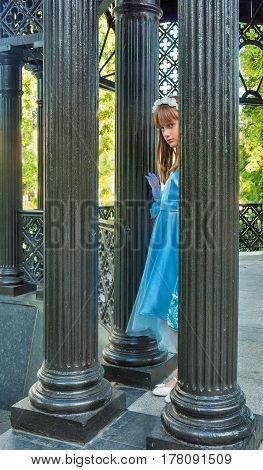 sad little girl in smart blue dress stands among the columns of beautiful park-gazebo