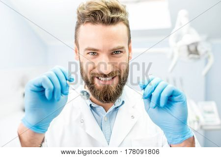 Portrait of scary dentist with dental tools looking to the mouth at camera