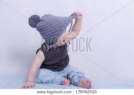 Delightful 10 month toddler boy sitting on the blue carpet and looking away