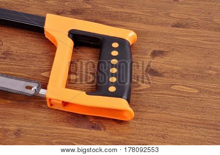 Hacksaw on wood on a wooden background background