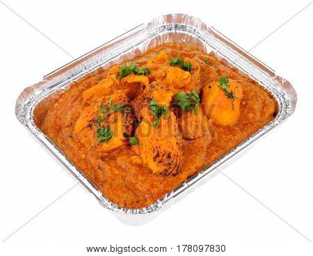 Creamy chicken tikka masala curry in a foil take away tray isolated on a white background