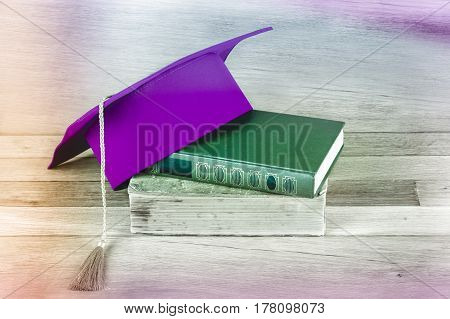 Graduation mortarboard on top of stack of books on the wooden table