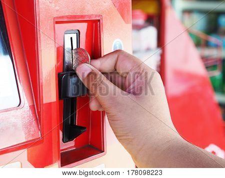 Close-up human hand inserting coin in red telephone vending machine Thailand.