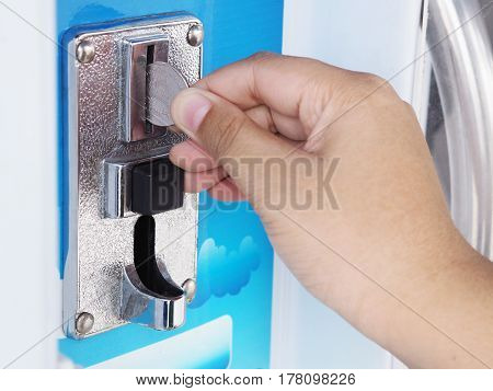Close-up human hand inserting coin in drinking water vending machineThailand