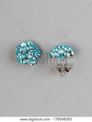 Pair of earrings with gems on grey background