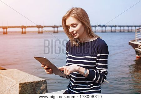 Attractive girl student reading electronic book on digital tablet while sitting near river port in sunny day woman watching video on portable touch pad connected to network during her recreation time