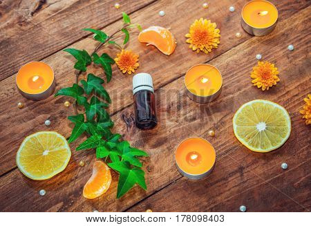 Citrus and herbs aroma oil concept. Essential glass bottle, burning yellow aroma candles, orange daisy flowers, tangerine, lemon slice and ivy branch with green leaves on a wooden background