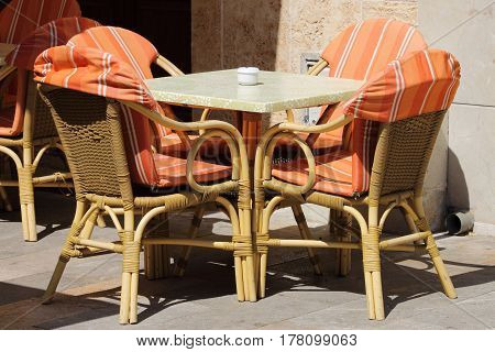 Wicker chairs and table in a street cafe