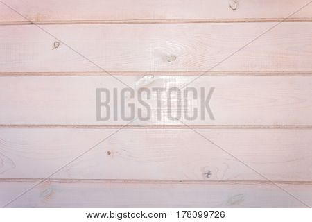 Wooden background. Pale-pink painted horizontal planks. Texture of wood shows through paint .