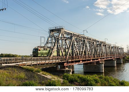 Railway bridge through the river Volga and freight train is moving on it in summer day in Syzran Russia.