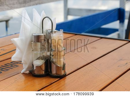 Set in a cafe: pepper, salt, toothpicks and napkins on wooden table.