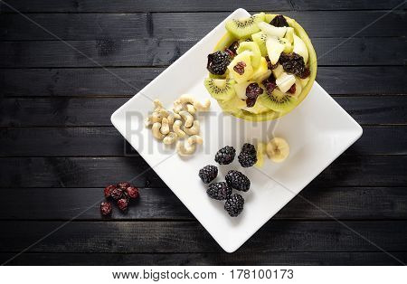 Variety of fruits and nuts on a black table top view. Concept of health and nutrition