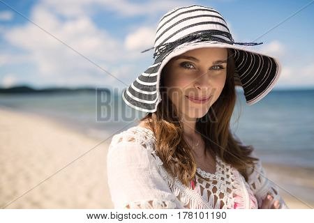Classic Beautiful Woman In Hat Standing On Beach Smirking