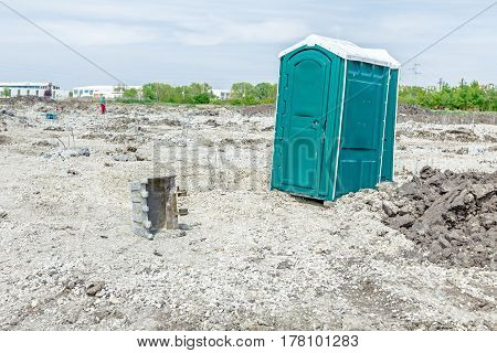 Two transportable public street toilets are placed at building site outdoor privacy.