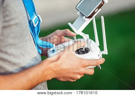 Drone remote control in hand of a man. Man in a black shirt operating of flying drone
