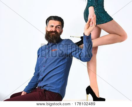 bearded man long beard brutal caucasian hipster with moustache on smiling face with female sexy legs in fashionable shoes and green sequins skirt isolated on white background getting haircut