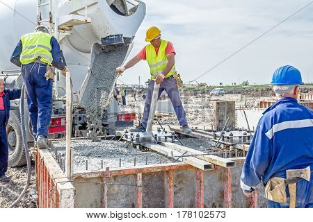 Zrenjanin Vojvodina Serbia - April 30 2015: Workers at building site are pouring concrete in mold from mixer truck.