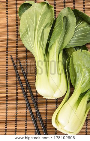 Bunch Of Fresh Green Baby Bok Choy With Chopsticks , On Bamboo Placemat Background