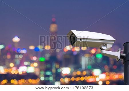Single CCTV Security camera on Blurred night downtown city building background with light bokeh scene.