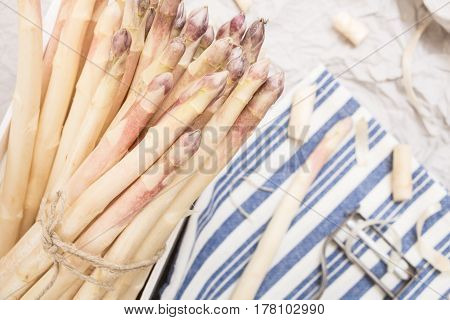 Bunch Of White Asparagus, On Crumpled Paper With Metallic Peeler And Kitchen Towel.