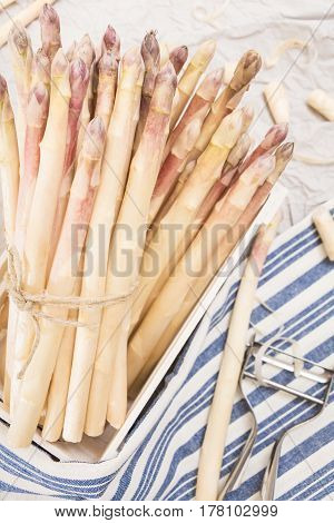 Bunch Of White Asparagus In Box, On Crumpled Paper With Metallic Peeler And Kitchen Towel.
