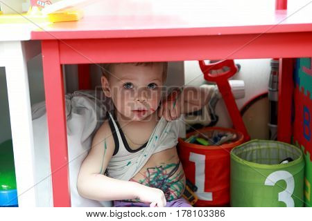 Portrait of painted boy under a table